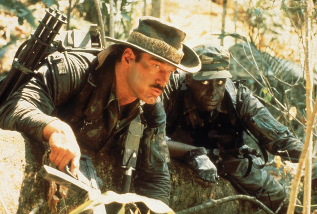 Bill Duke als Sergeant Mac Eliot und Jesse Ventura als Blaine liegen im Dschungel auf der Lauer mit gezückten Waffen