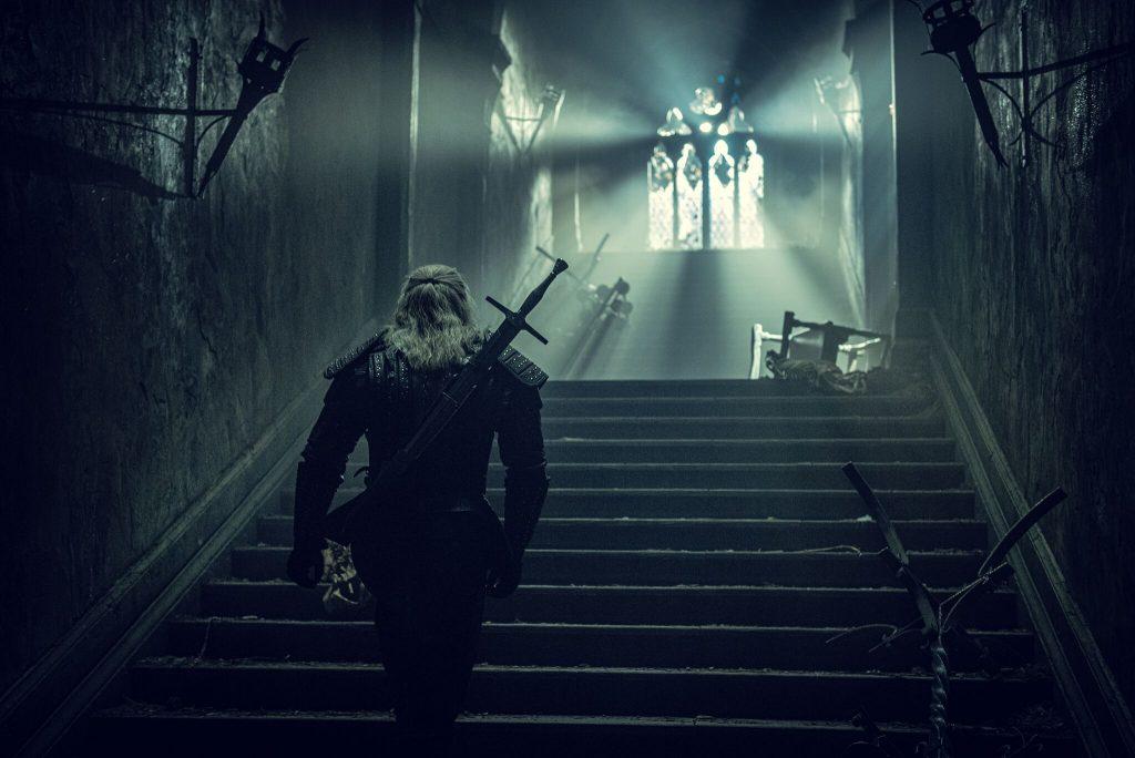 Henry Cavill geht als Geralt von Riva eine Treppe hoch, schummriges Licht, Verwüsteter gang
