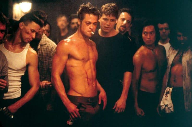 Tyler Durden (Brad Pitt) mit nacktem Oberkörper steht inmitten einer Gruppe von Männern in einem dunklen Raum. Er hat ein blaues Auge und eine Zigarette zwischen den Lippen