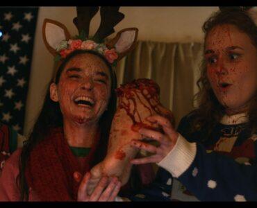 In kitschiger Weihnachtskleidung und blutbespritzt werden drei sichtlich amüsierte Personen gezeigt. Die Frau auf der rechten Seite des Bildes hält einen abgetrennten Fuß in ihren Händen.