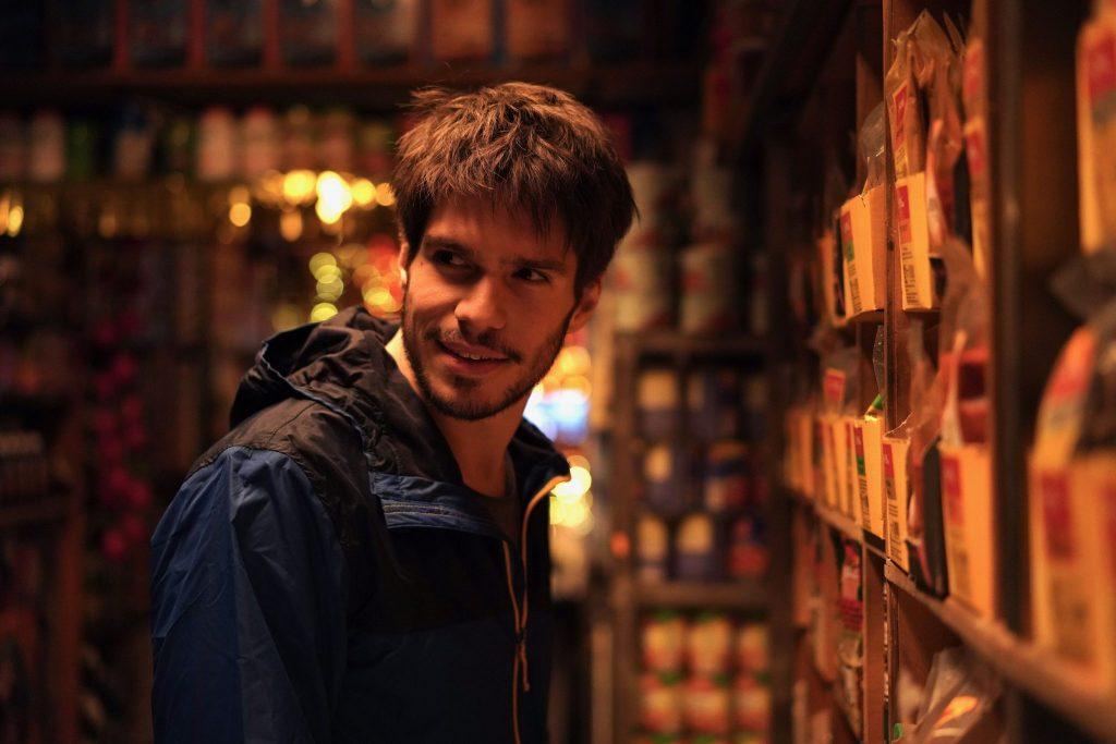 Rémy steht unentschlossen vor einem Einkaufsregal in Einsam Zweisam