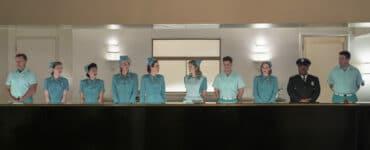 Die gesamte Belegschaft der Nervenheilanstalt in Ratched steht nebeneinander hinter der Rezeption im Empfangsbereich.