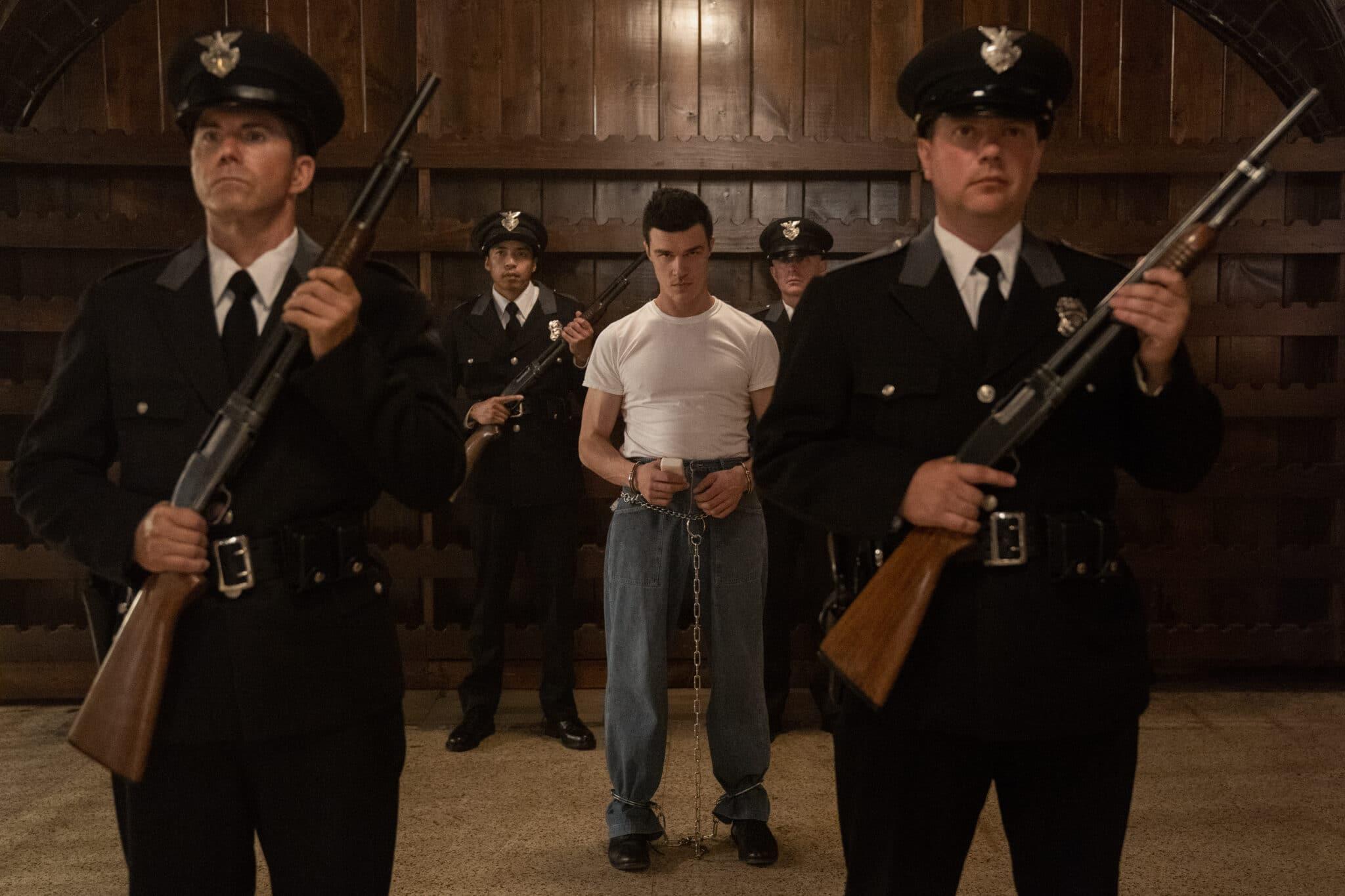 Vier Wachmänner umstellen Edmund Tolleson (Finn Wittrock) mit erhobenen Flinten in einer Scheune. Der Gefangene ist an Händen und Füßen gefesselt.