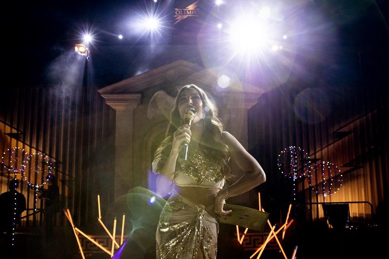 Eine Ansagerin im goldenen Abendkleid steht im Scheinwerferlicht mitten in der Arena in Reality Z - Neu auf Netflix im Juni 2020