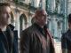 Ryan Reynolds, Dwayne Johnson und Gal Gadot nebeneinander vor einer historischen Gebäudefront.