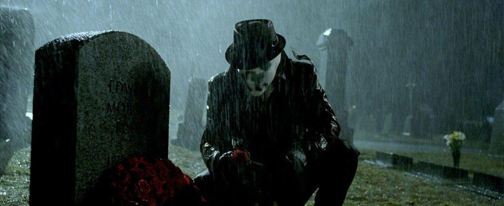 Rorschach sitzt vor einem Grabstein mit Rosen, es regnet stark