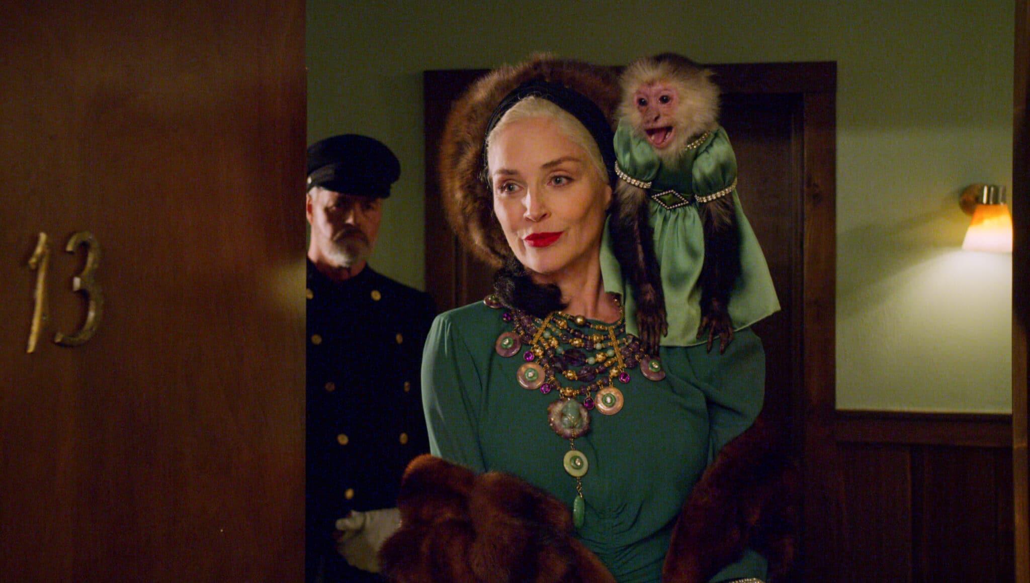 Lenore Osgood (Sharon Stone) öffnet in einem extravaganten Outfit mit einem Äffchen auf der Schulter die Tür zu ihrer Wohnung. Im Hintergrund steht ein Wachmann in Uniform.
