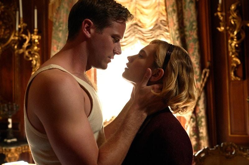 Ein Mann greift einer Frau leidenschaftlich an den Nacken, dreht ihren Kopf für einen Kuss zu ihm in Rebecca - Neu auf Netflix im Oktober 2020