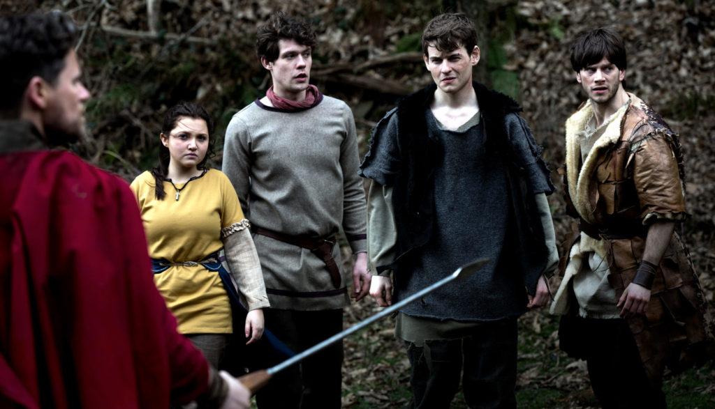 Enica, gespielt von Mia Mckenna-Bruce, Julian, gespielt von Richard Mason, Culain, gespielt von Tom Leach und Sego, gespielt von Gwydion Rhys stehen einem Legionär gegenüber, der sie mit einer Lanze bedroht.