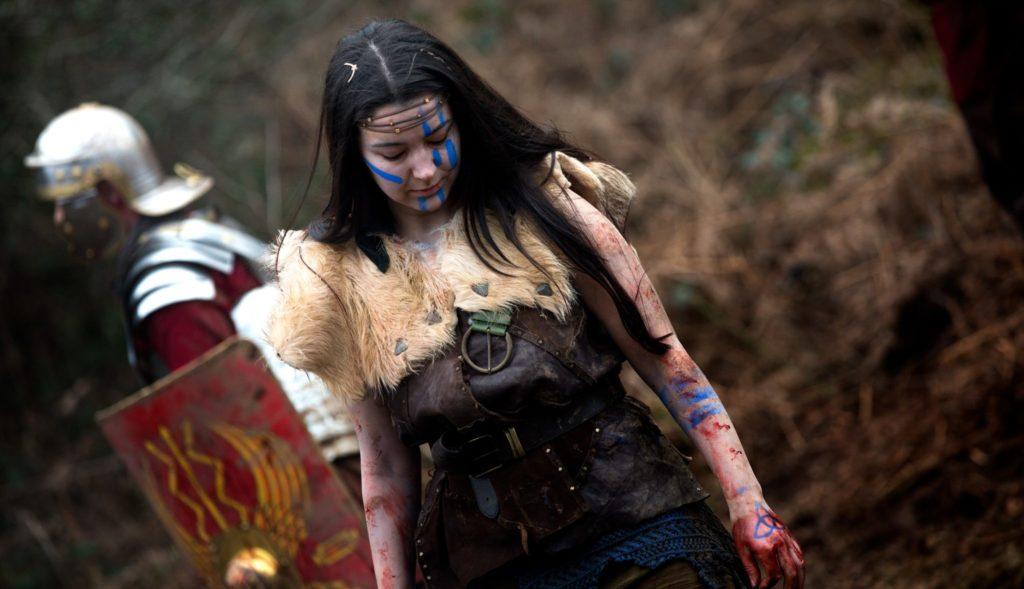 Eine junge Waliserin in Kriegsbemalung steht in Rebellion - Der Zorn des Römischen Reichs vor einem Legionär, der ihr den Rücken zuwendet.