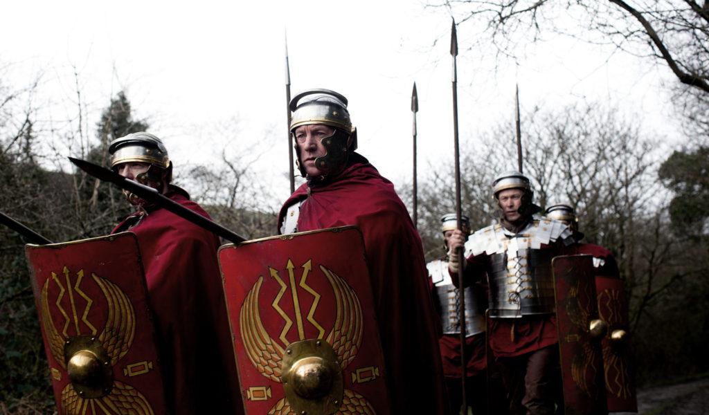 Römische Legionäre in Kampfposition. Die beiden Vorderen haben die Lanzen gesenkt und die Schilde gehoben.