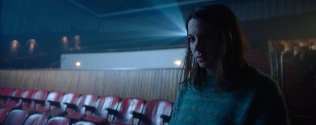 Ana kommt mit besorgtem Gesicht in den Kinosaal, während der Projektor hinter ihr noch läuft - Red Screening