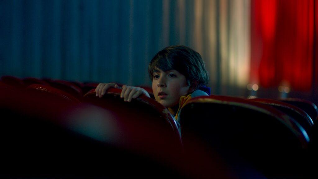 Ein kleiner Junge lugt ängstlich über seinen Kinosessel nach hinten - Red Screening