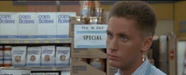 Emilio Estevez trägt eine weiße Supermarkt-Arbeitsuniform mitsamt schwarzer Fliege, außerdem eine blonde Kurzhaarfrisur und einen Kreuzohrring. Er steht vor einem Regal mit verschiedenen Dosen und blickt aggressiv zu einer Person außerhalb des Bildes.
