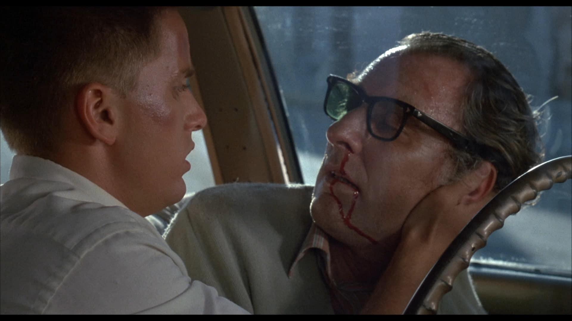 Emilio Estevez sitzt neben einem Mann mit nach hinten gekämmten Haaren und schwarzer Hornbrille in einem Auto. Der Mann ist bewusstlos und blutet aus Mund und Nase. Emilio hält seinen Kopf fest und begutachtet sein Gesicht.