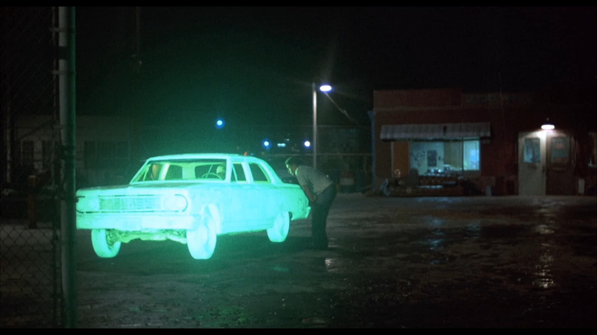 Emilio Estevez steht auf einem dunklen Hofgelände und schaut gebeugt in das Fahrerfenster eines Cadillac, der grün leuchtet.
