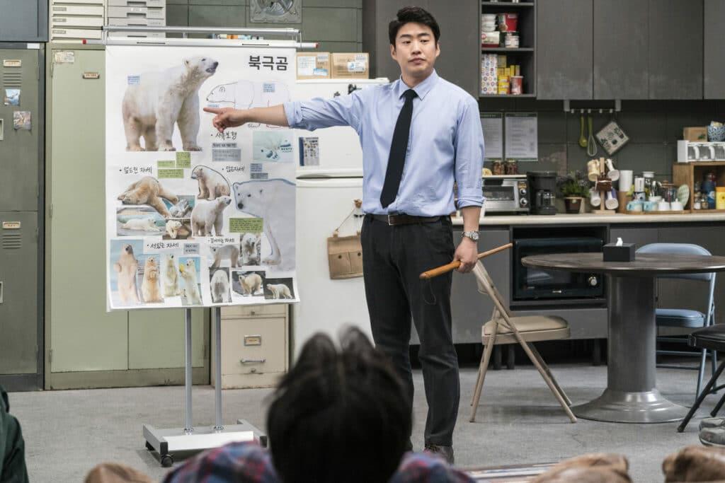 """Kang (Ahn Jae-hong) macht in """"Rettet den Zoo"""" seine Angestellten mit den Tieren vertraut. Auf dem Bild steht er vor den Mitarbeitern und zeigt auf ein aufgehängtes Bild mit einem Eisbären."""