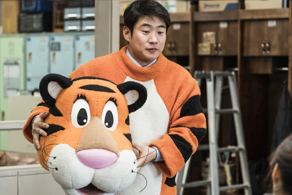 """Kang (Ahn Jae-hong) kommt eine geniale Idee. Die Angestellten sollen in """"Rettet den Zoo"""" in die Rollen der Tiere schlüpfen. Auf dem Bild ist der junge Mann in einem Tigerkostüm zu sehen, dass eher wie aus einem Comic als authentisch wirkt. Dieses ist knall orange und mit großen Augen sowie einer rosa Nase versehen."""