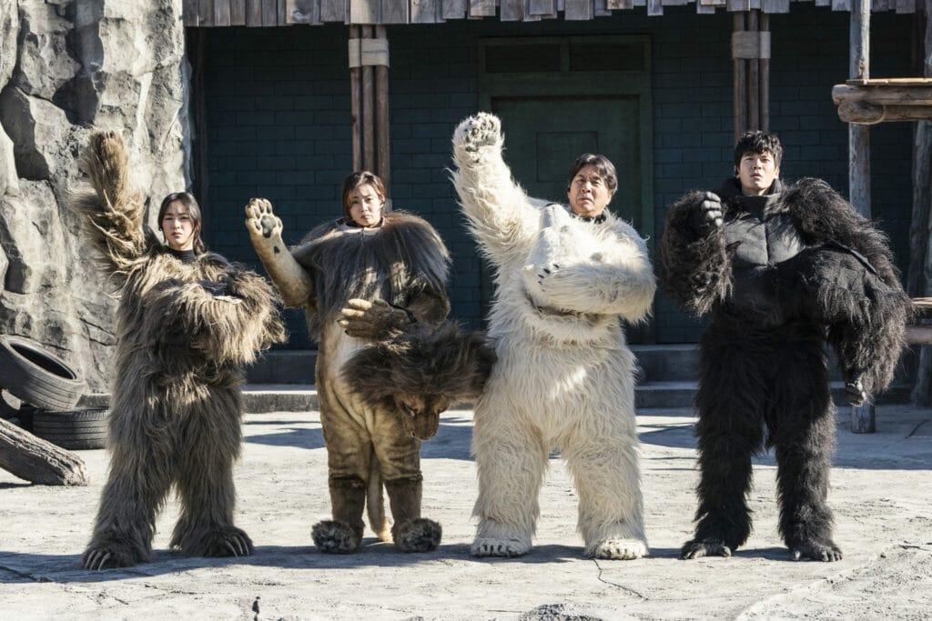 """Auf dem Bild sind die Zoo-Angestellten in ihren Tierkostümen in """"Rettet den Zoo"""" zu sehen. Alle stehen nebeneinander in einem Gehege, die beiden männlichen Darsteller stehen rechts, die beiden Damen links. Die Männer tragen die Kostüme vom Eisbären und Gorilla, die Frauen vom Löwen und vom übergroßen Faultier. Die Köpfe ihrer Kostüme halten sie dabei noch in den Händen. Alle heben dabei noch eine Hand."""