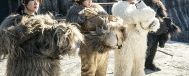 """Auf dem Bild sind die Zoo-Angestellten in ihren Tierkostümen in """"Rettet den Zoo"""" zu sehen. Alle stehen nebeneinander in einem Gehege, die beiden männlichen Darsteller stehen rechts, die beiden Damen links. Die Männer tragen die Kostüme vom Eisbären und Gorilla, die Frauen vom Löwen und vom übergroßen Faultier. Die Köpfe ihrer Kostüme halten sie dabei vor sich in beiden Händen. Alle blicken geradeaus auf etwas oder jemanden außerhalb des Geheges."""