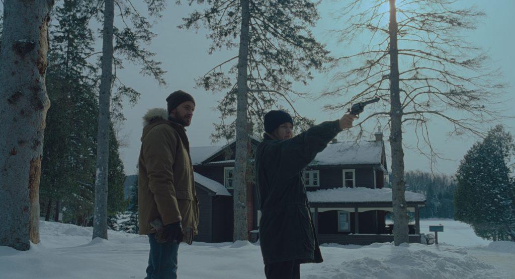 Richard (Richard Armitage) zeigt seiner Verlobten im schneebedeckten Wald, wie man mit einer Waffe umgeht in The Lodge © 2019 SquareOne Entertainment