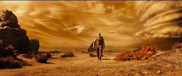 Riddick (Vin Diesel) ist hier mal wieder als Einzelkämpfer unterwegs. Er steht inmitten einer trostlosen Wüste. Der Himmel ist ebenfalls in einem sandigen orange gefärbt. - Riddick-Podcast