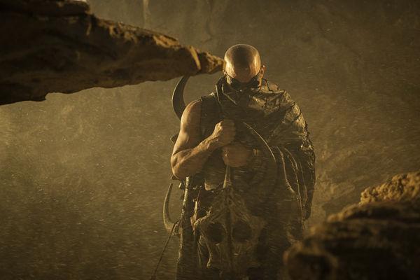Richard B. Riddick (Vin Diesel) steht in einer Höhle und vermummt mit einem Cape sein Gesicht. - Riddick-Podcast