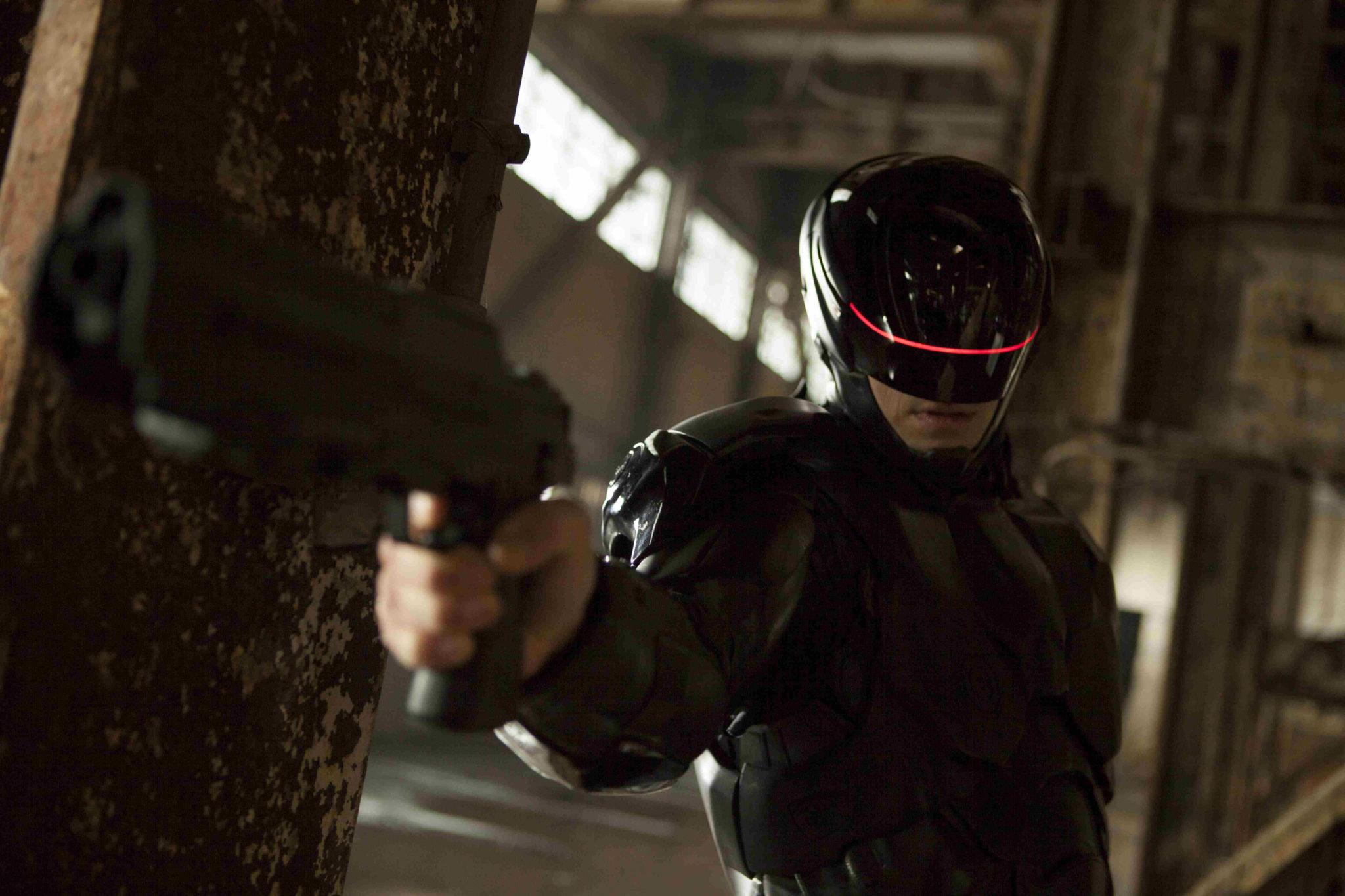 """Joel Kinnaman als """"RoboCop"""" richtet im gleichnamigen Film von 2014 seine Waffe in einer Lagerhalle stehend auf die Kamera."""