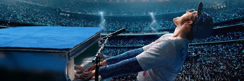 Elton John (Taron Edgerton) spielt in einem schillernden Kostüm und mit Baseballcap in einem vollen Stadion an einem blauen Flügel und singt lauthals.