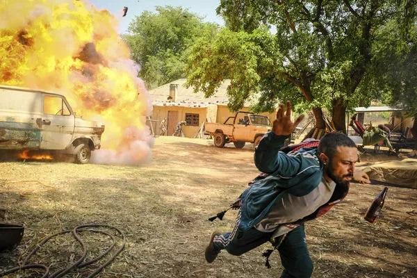 In der Anlage der Terroristen explodieren Autos und Gebäude, während diese davor flüchten.