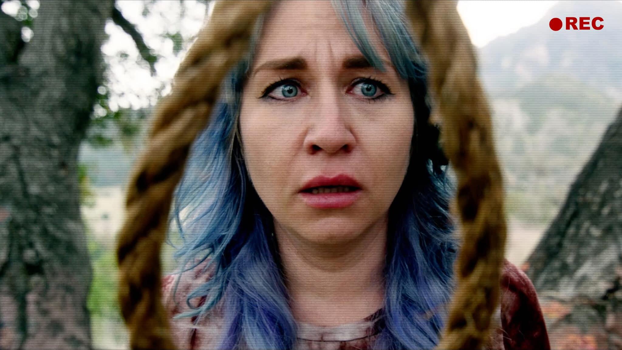 Elissa Dowling hat blaugefärbe lange Haare und schaut schockiert durch eine Seilschlinge, die blutvorschmiert vor ihr baumelt.