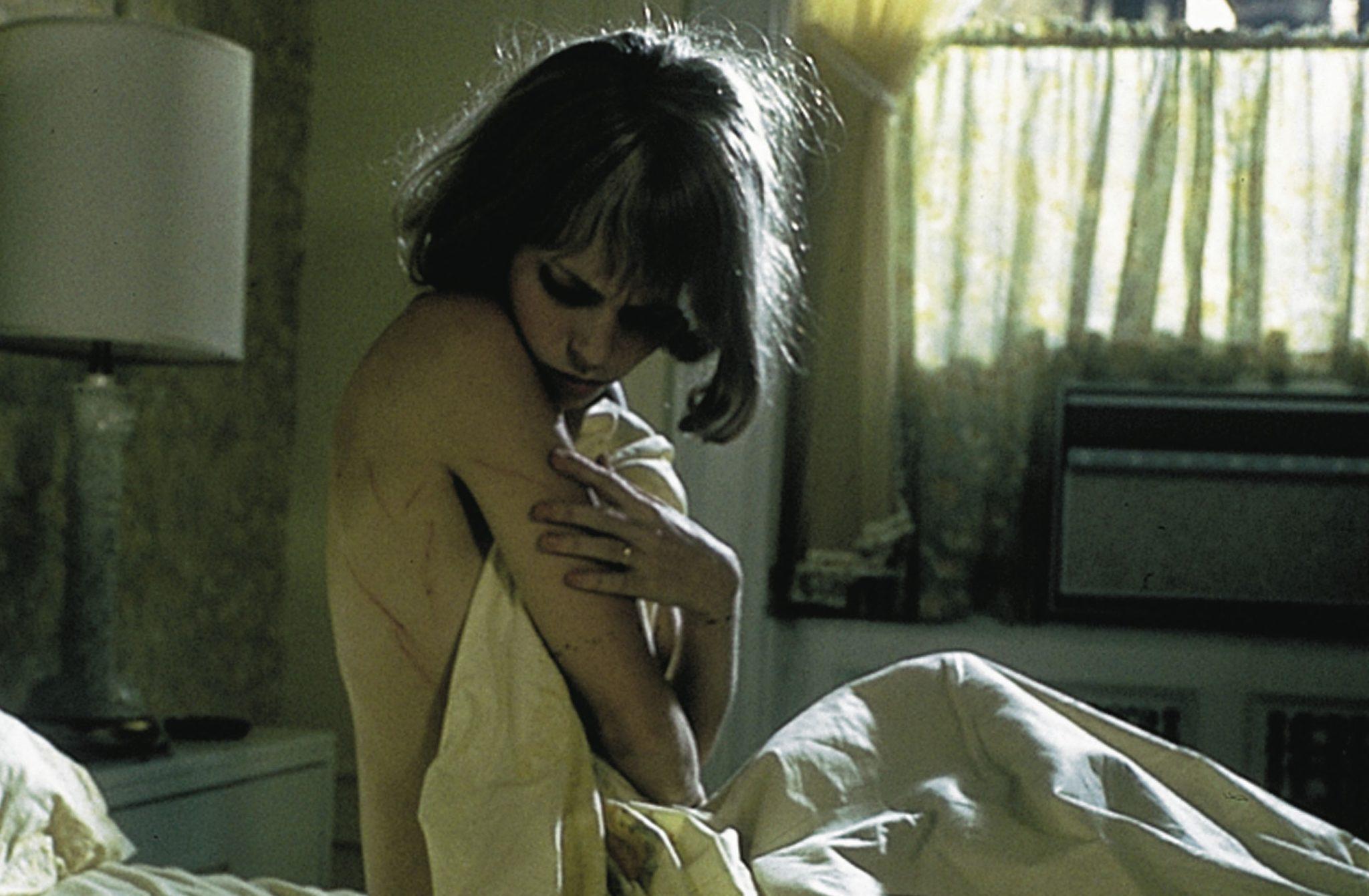 Rosemarie Woodhouse (Mia Farrow) sitzt im Bett und betrachtet überfordert die zahlreichen Schnittwunden an ihrem Körper.
