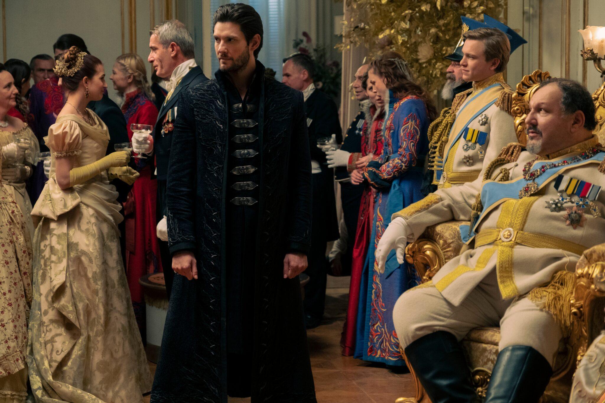 Kirigan (Ben Barnes) steht in einem schwarzen Mantel zwischen zahlreichen festlich, aber bunt gekleideten Personen bei einer Feierlichkeit. Rechts im Bild sitzt der König in seinem Thron. Er trägt ein Beiges Outfit mit zahlreichen Ehrenzeichen. Im Hintergrund sieht man weitere Feiergäste.