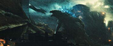 """Das Bild zeigt eine Szene aus dem Film """"Godzilla 2: King of the Monsters"""", wo sich die titelgebende Riesenechse Godzilla und der dreiköpfige Drache Ghidorah zu sehen, die sich vor einem malerischen Hintergrund anfauchen - Streamcatcher Podcast Februar 2021."""