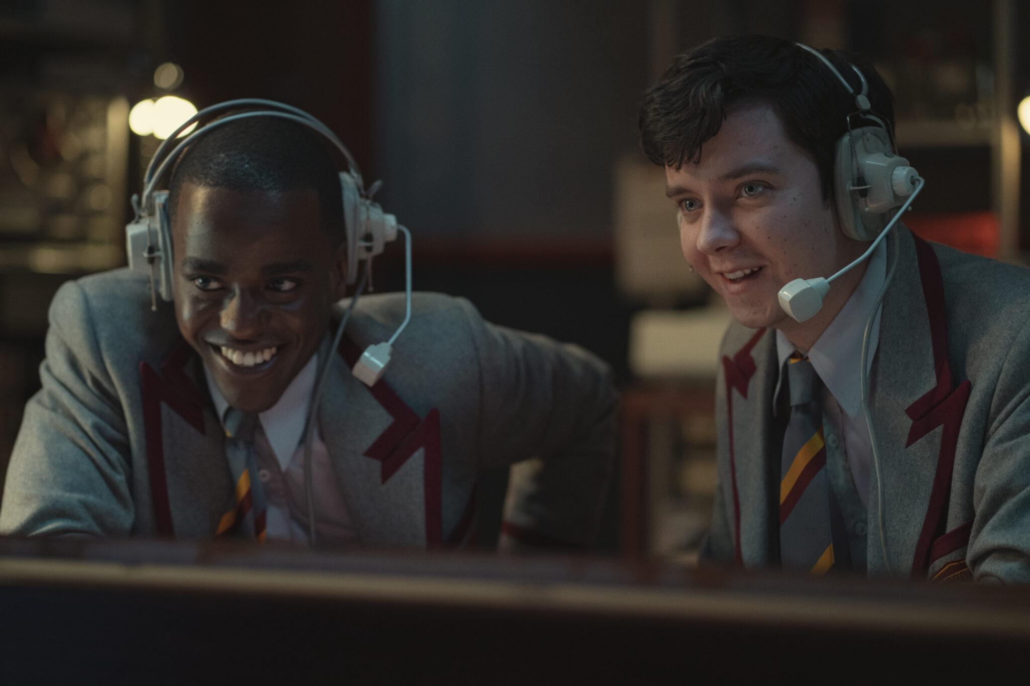 Eric und Otis sitzen in Schüleruniform hinter einem Computerbildschirm und tragen beide Headsets. Beide lächeln.