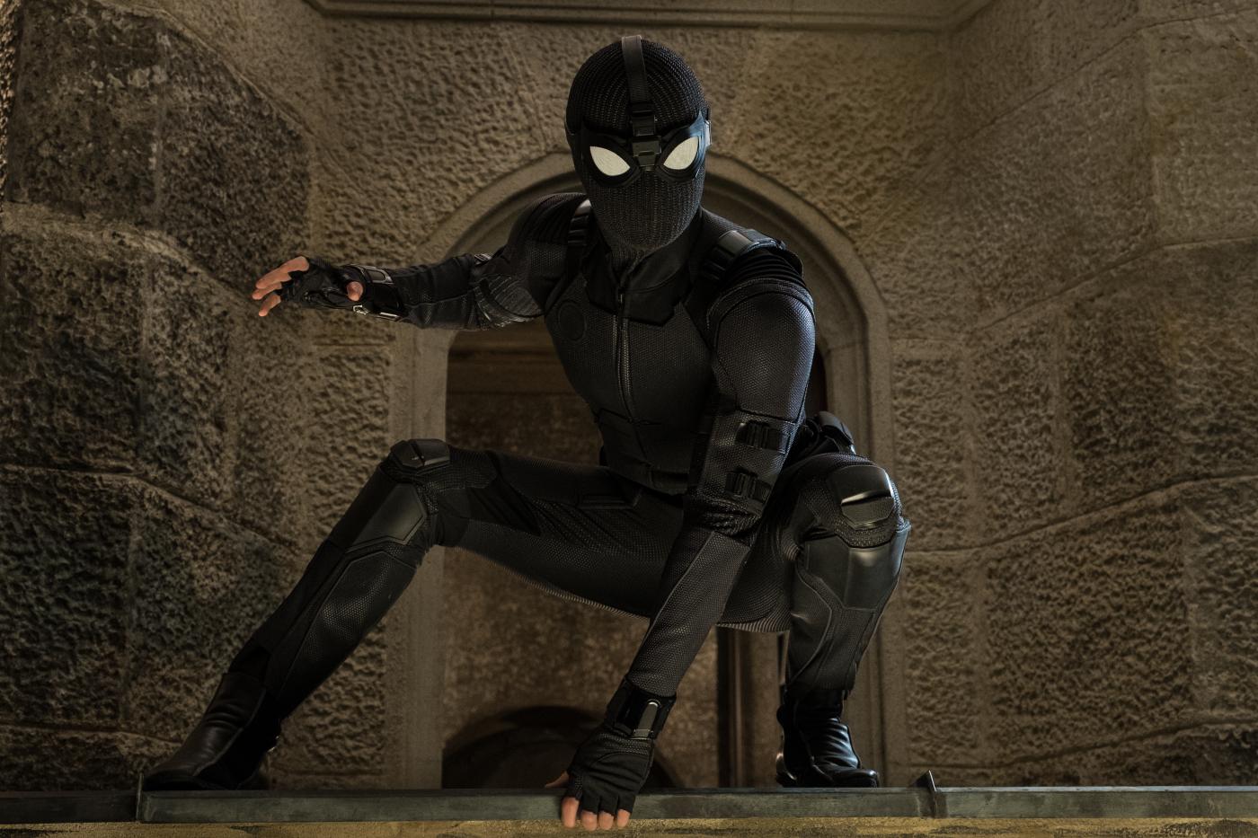 Tom Holland als Spider-Man in einem schwarzen Kostüm in Heldenpose.