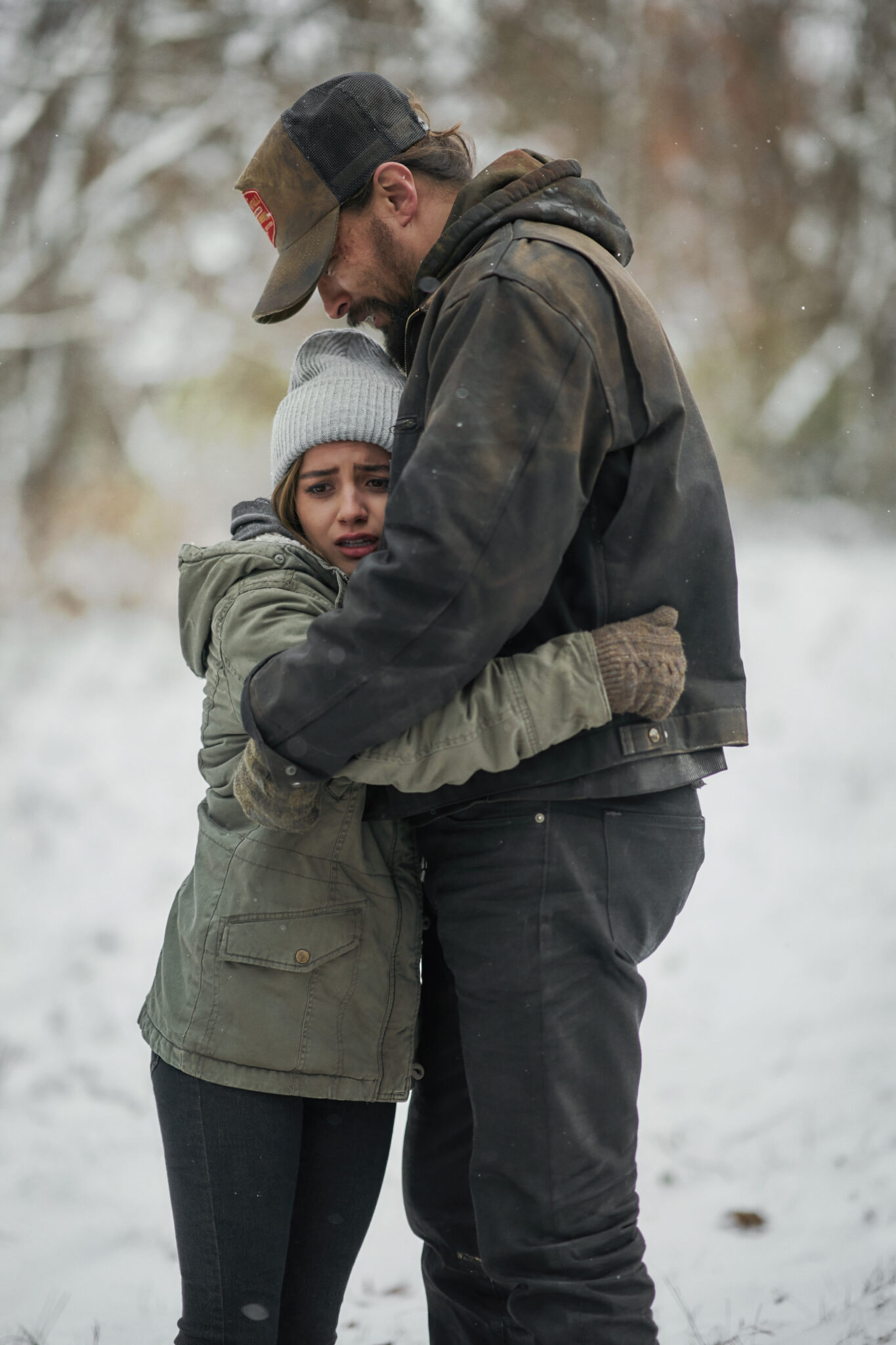 Rachel und Ray Cooper umarmen sich auf einer zugeschneiten Wiese. Er trägt eine schmutzige Lederjacke, dunkle Hosen und eine Trucker-Cap, sie ebenfalls dunkle Hosen, eine Olive Jacke und eine graue Mütze.