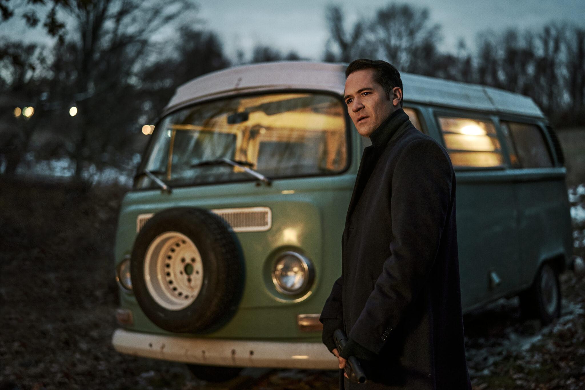Manuel Garcia Rulfo steht vor einem alten, hellblauen Bus in schwarzem Mantel.