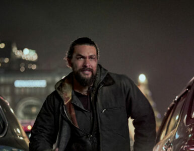 Jason Momoa als Ray Cooper nachts zwischen zwei Autos auf offener Straße. Im Hintergrund Hochhäuser.