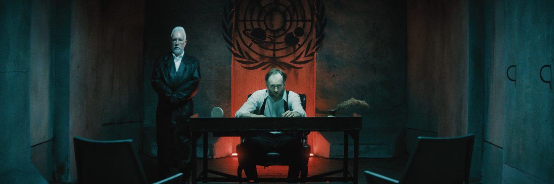 Der alte Präsident der Welt, gespielt von Mark Ashworth, sitzt in einem düsteren Raum an einem Schreibtisch vor einer rot erleuchteten Nische, flankiert von einem Wächter.