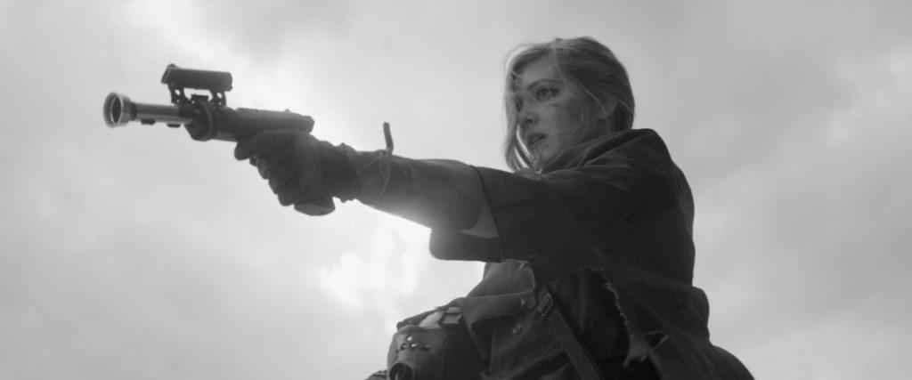 Sarah, gespielt von Shannon Hutchinson, hält eine futuristische Waffe im Anschlag.