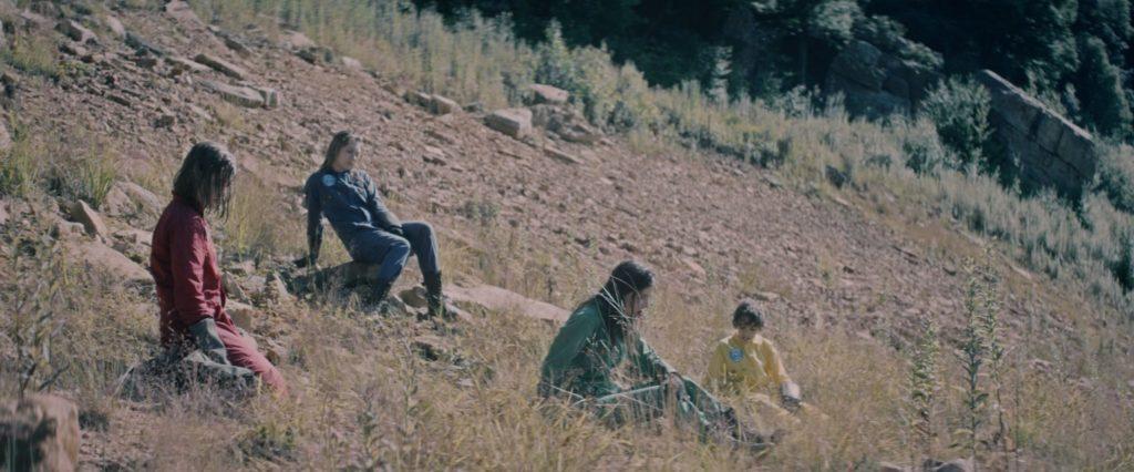 Sarah, gespielt von Shannon Hutchinson,Charlie, gespielt von Jasmina Parent, Brooke, gespielt von Yael Haskal, und Tom, gespielt von Jonathan Newport, sitzen in Space Assassins - Flucht in die Zukunft auf einem Geröllhang.