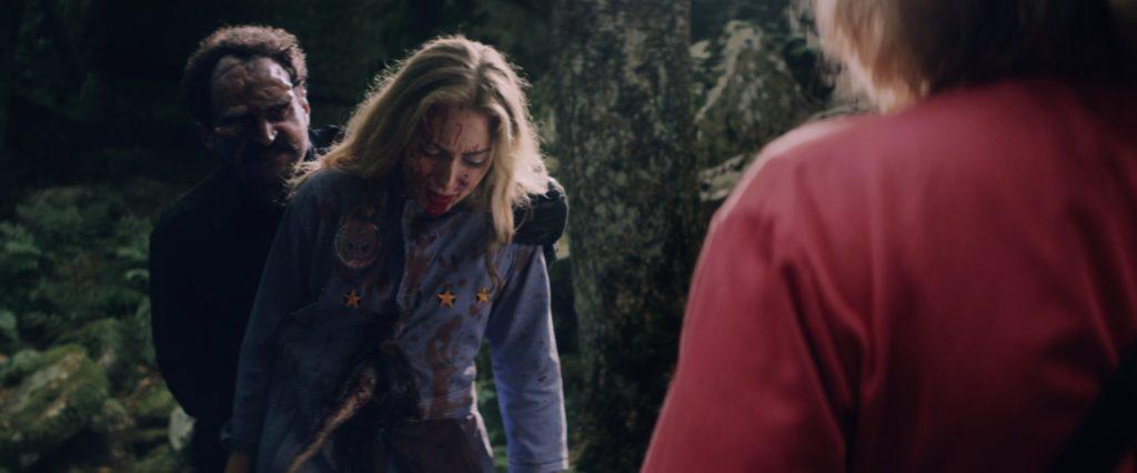 Der mutierte Commander, gespielt von Vito Trigo, steht hinter Charlie, gespielt von Jasmina Parent und bedroht sie. Sarah, gespielt von Shannon Hutchinson, will helfen.