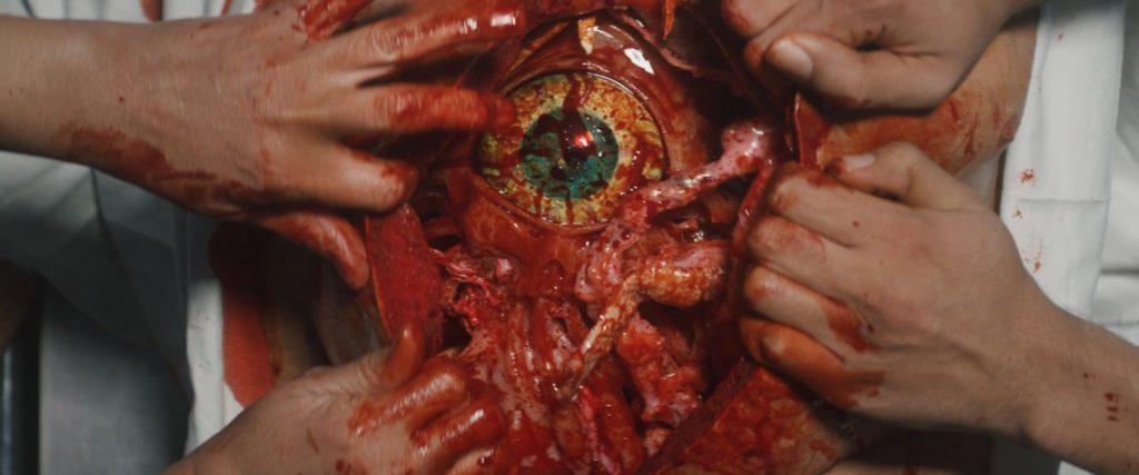 Im geöffneten Bauchraum erscheint unter Blut und Gedärme ein riesiges Auge - die Zeitkapsel.