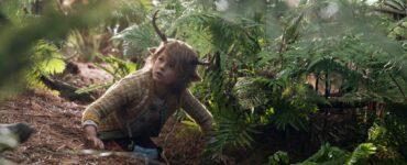 Gus (Christian Convery) kniet im Wald auf dem Boden. Er trägt ein Hirschgeweih auf dem Kopf und eine karierte Weste. Um ihn herum ranken zahlreiche Farne.