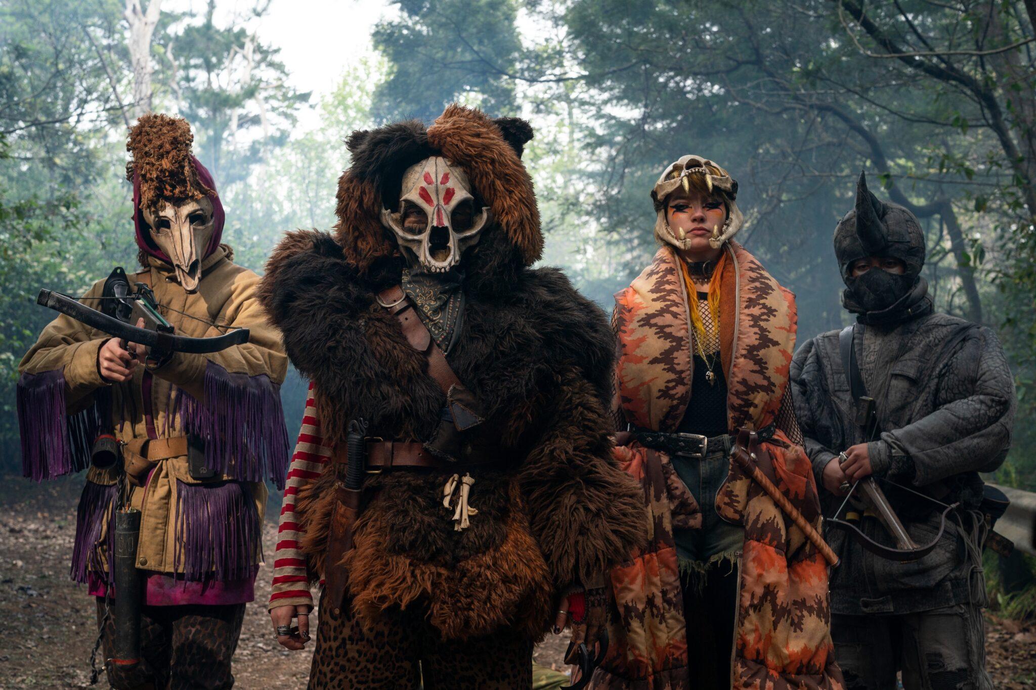 Vier Mitglieder der Armee der Tiere mit aufwändigen Kostümen im Wald. Sie tragen jeweils Tierschädel als Marken und sind bewaffnet mit Armbüsten und Messern.