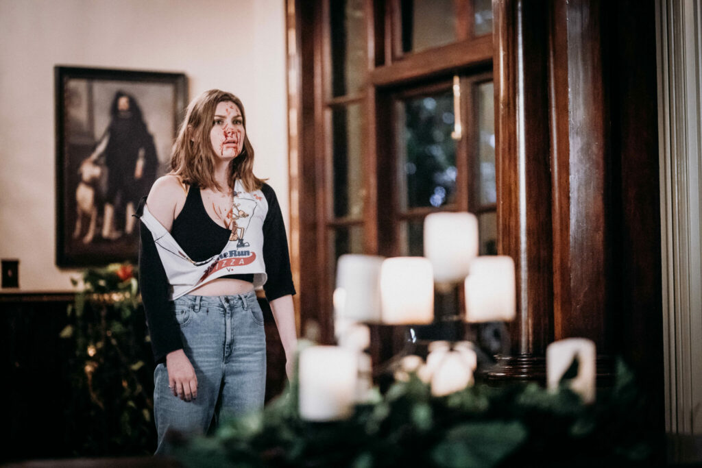 Samantha steht auf der linken Seite eines Raumes. Mit zerrissenem Shirt und blutverschmiertem Gesicht blickt schockiert zur vorderen, rechten Bildhälfte. Im Bildhintergrund befindet sich links ein Gemälde und rechts ein alter Schrank, der einen Großteil des Bildes einnimmt. Im Vordergrund befindet sich ein Kerzenständer mit mehreren, weißen Kerzen.