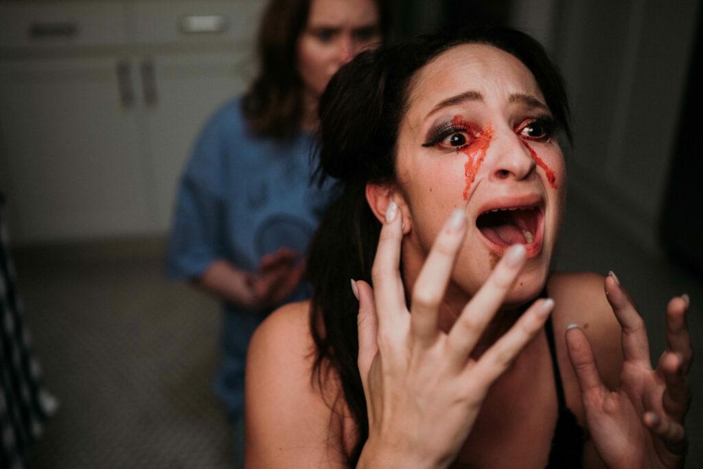 Eine Frau läuft Blut aus den Augen. Schockiert und schreiend blickt sie zur rechten Bildseite und hält sich die Hände gespreizt vor ihrem Kopf. Auf der linken Bildseite ist die Protagonistin im Hintergrund erkennbar.