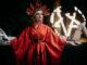 Die Antagonistin steht in roter Robe und mit imposantem Kopfschmuck bekleidet vor dem Opferaltar. Sie hält die Arme seitlich leicht nach oben gerichtet und hat den Blick leicht nach links geneigt. Im Hintergrund ist auf der rechten Seite ein brennendes Pentagramm erkennbar.