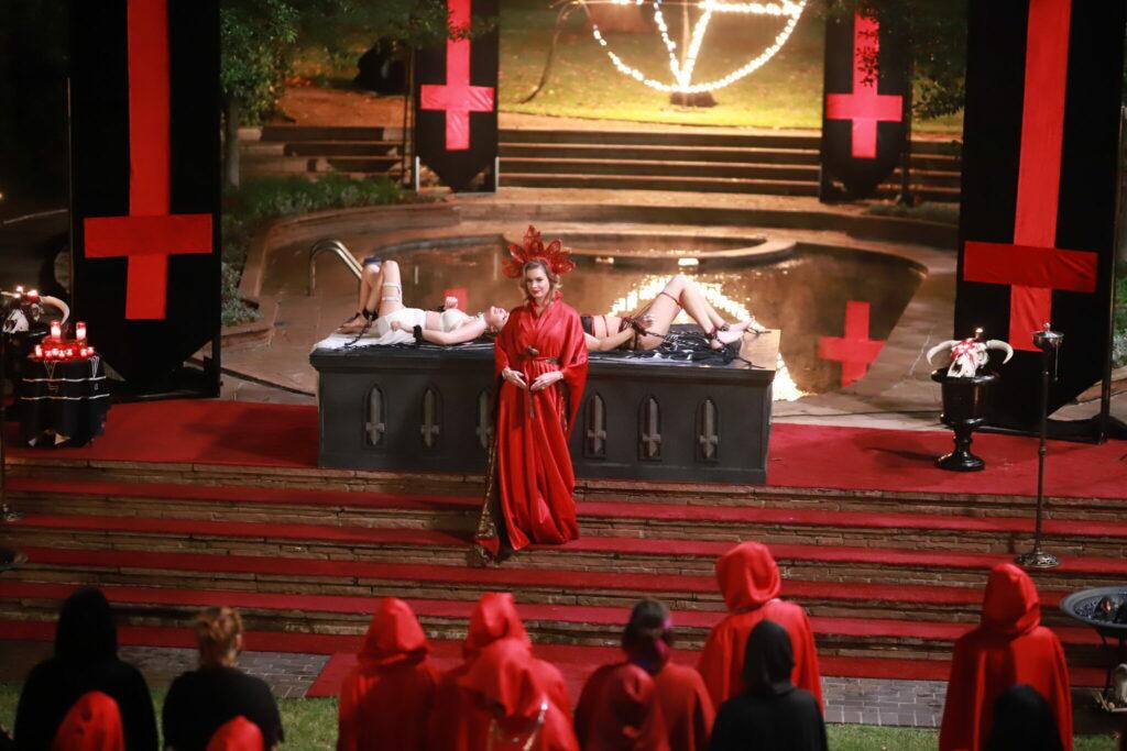 Die Antagonistin steht vor einem Altar vor ihren Anhängern. Diese sind zumeist in roten Roben gekleidet, zwei Personen tragen hingegen schwarze Roben. Im Hintergrund befinden sich zwei Frauen zur Opferung und mehrere umgedrehte Kreuze und ein brennendes Pentagramm.